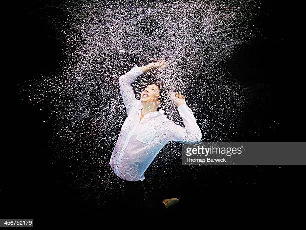 Businesswoman underwater amid air bubbles