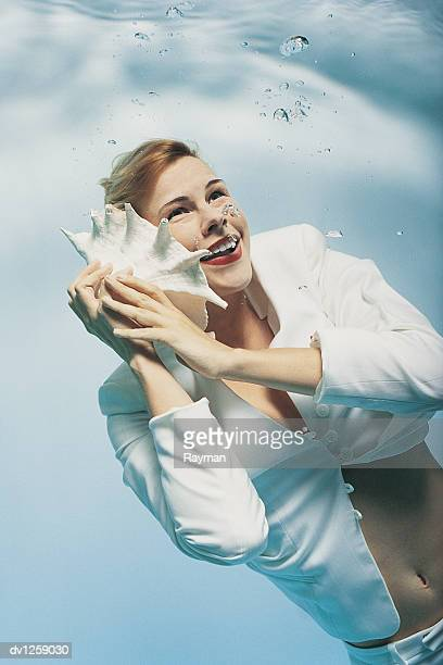 Businesswoman Underwater Holding a Seashell Pretending It's a Phone