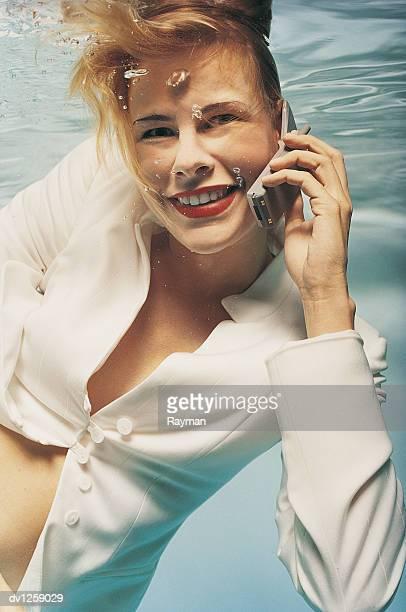 Businesswoman Underwater Using Her Mobile Phone
