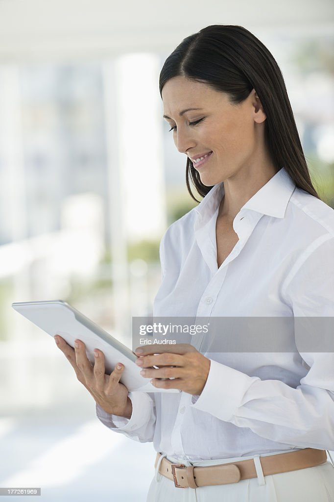 Businesswoman using a digital tablet in an office : Stock Photo