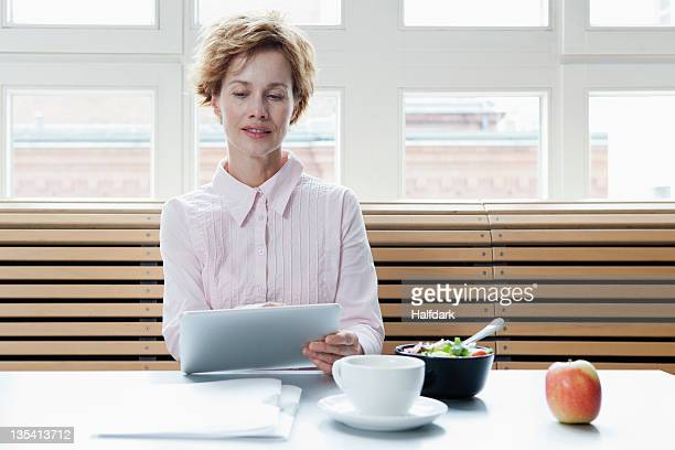 A businesswoman using a digital tablet on his lunch break