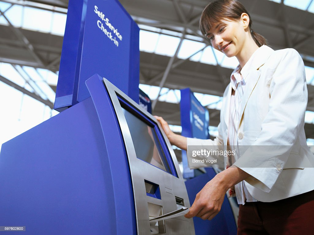 Businesswoman using a self-service check-in terminal at an airport