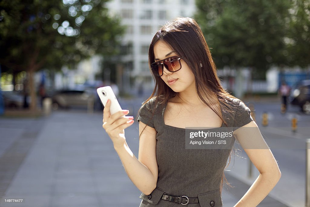 Businesswoman using a smart phone outdoors : Stock Photo