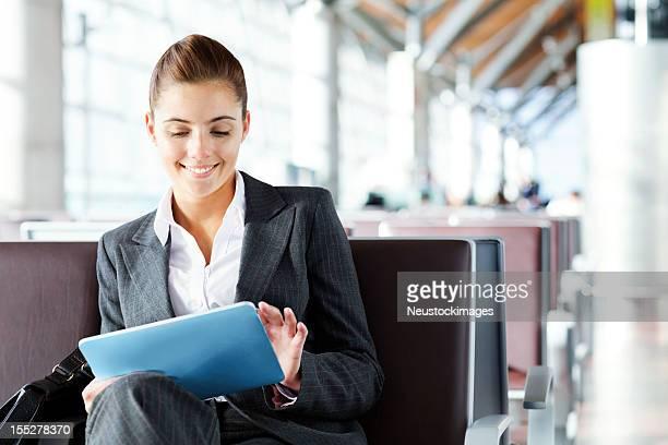 Femme d'affaires à l'aide d'une tablette ordinateur à l'aéroport