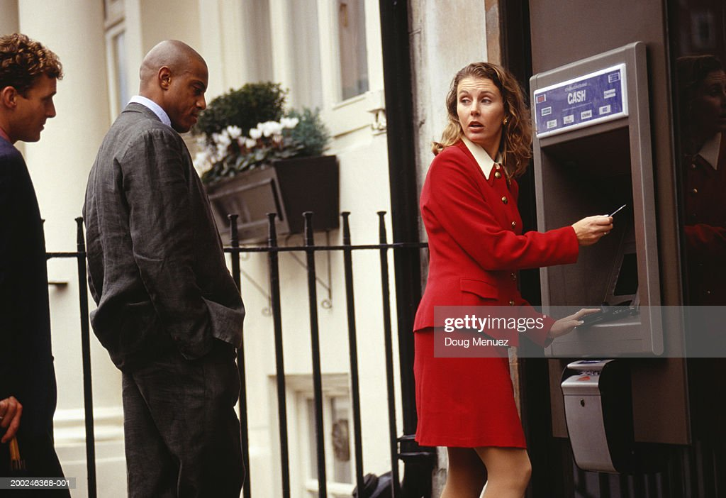 Businesswoman using ATM in street : Stock Photo
