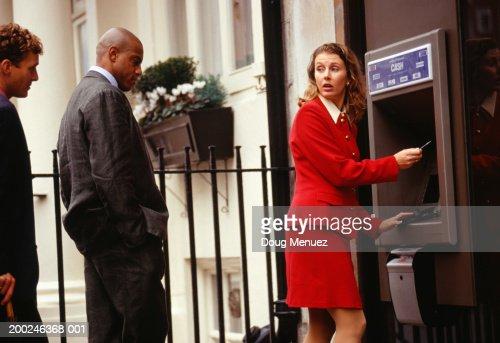 Businesswoman using ATM in street : Stock Photo