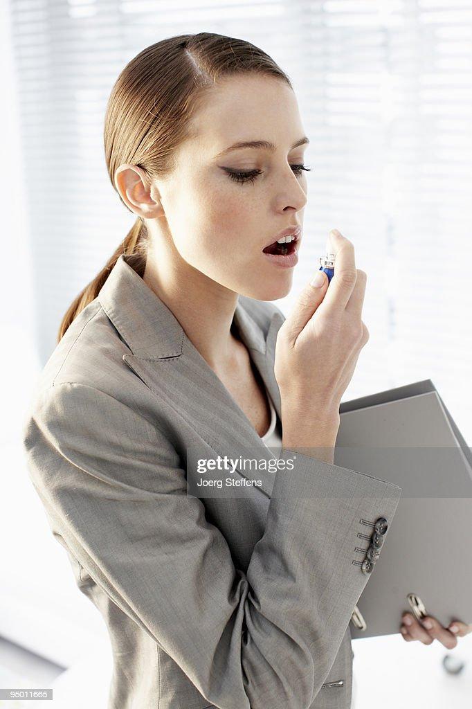 Businesswoman using breath spray : Stock Photo