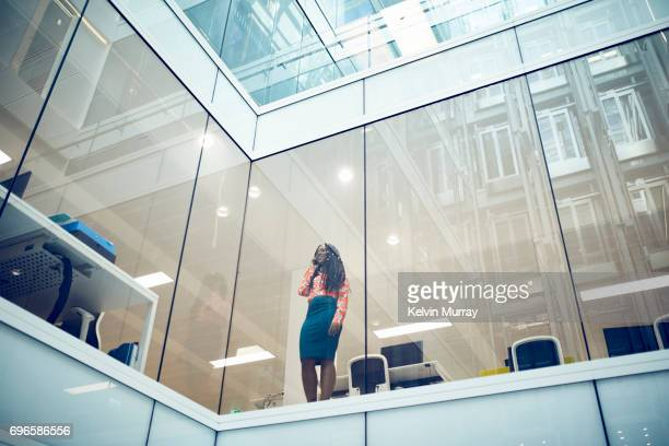 Businesswoman using cell phone by window in modern office