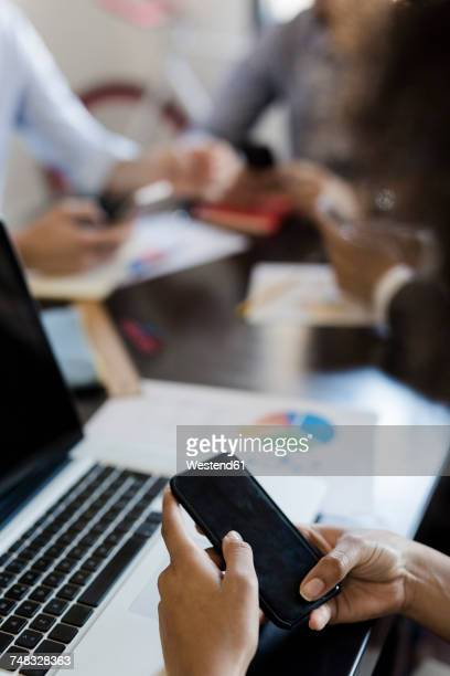 Businesswoman using cell phone during a meeting in office