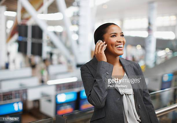Businesswoman using cell phone in airport
