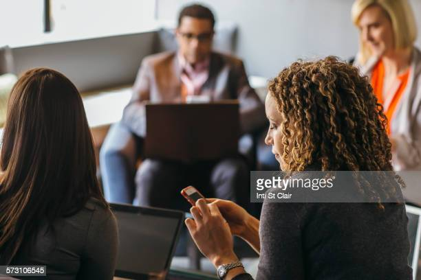 Businesswoman using cell phone in office meeting