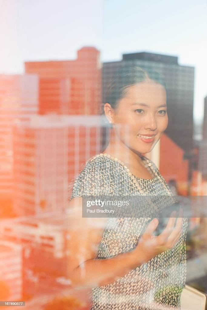 Businesswoman using cell phone in office : Stock Photo