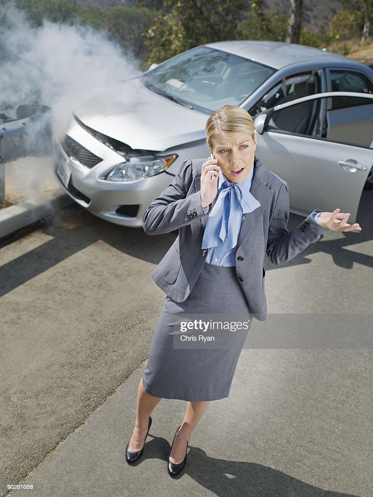 Businesswoman using cell phone near car wrecked on guardrail : Stock Photo