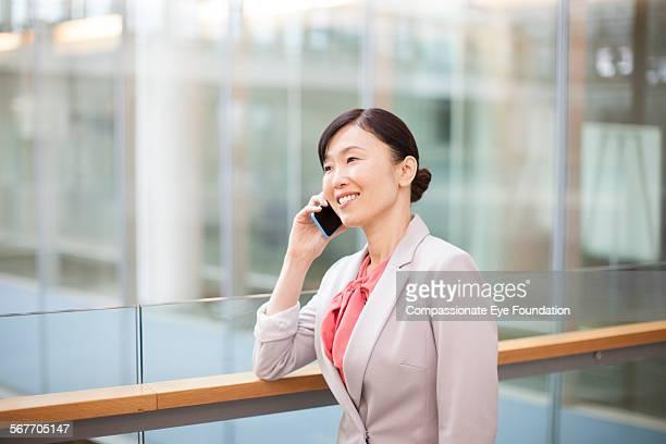Businesswoman using cell phone on atrium balcony