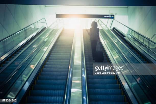 Businesswoman using cell phone on escalator