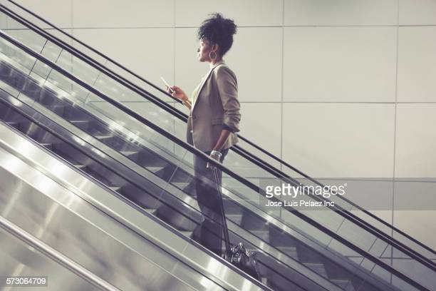 Businesswoman using cell phone on escalator