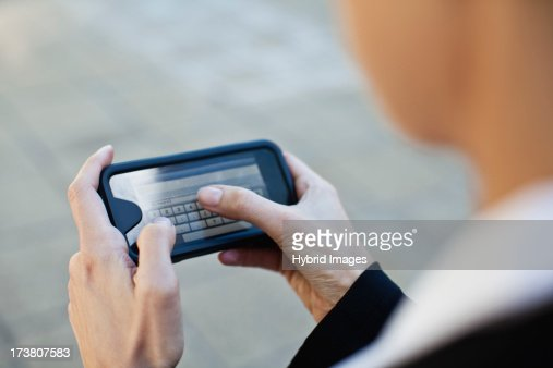 Businesswoman using cell phone outdoors : Stock Photo