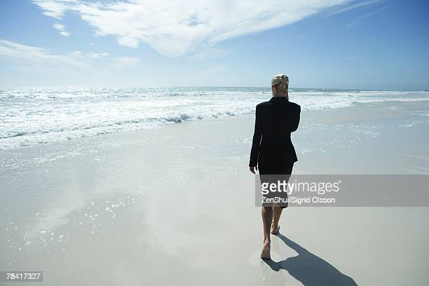 Businesswoman using cell phone, walking barefoot across beach, full length, rear view