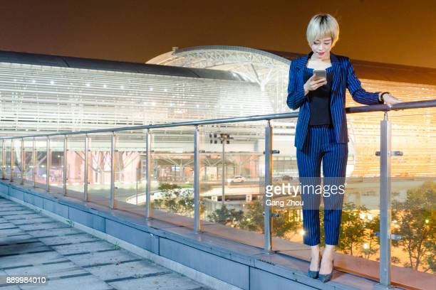 businesswoman using cellphone at footbridge of airport/station