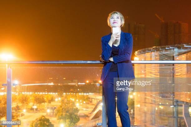 Geschäftsfrau mit Handy am Steg von Flughafen/Bahnhof