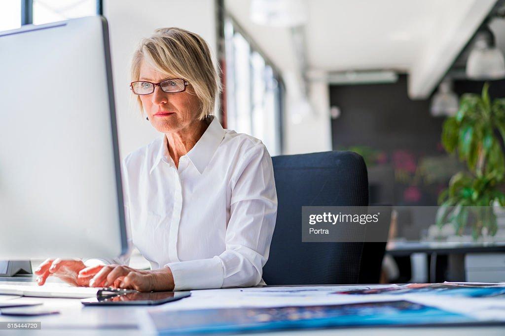 Donna d'affari utilizzando computer alla scrivania in ufficio : Foto stock
