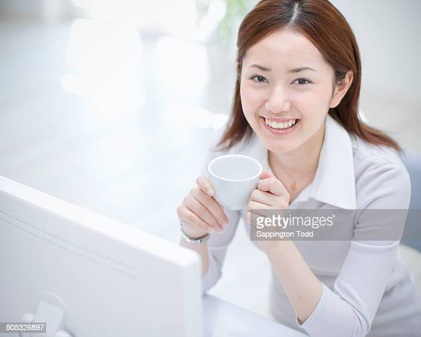 Businesswoman Using Computer With Mug In Hand