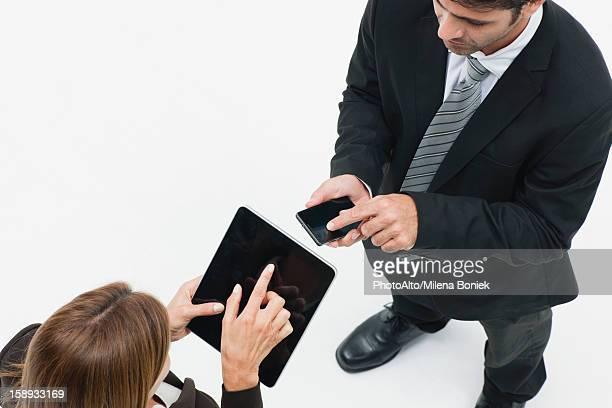 Businesswoman using digital tablet, businessman using smartphone