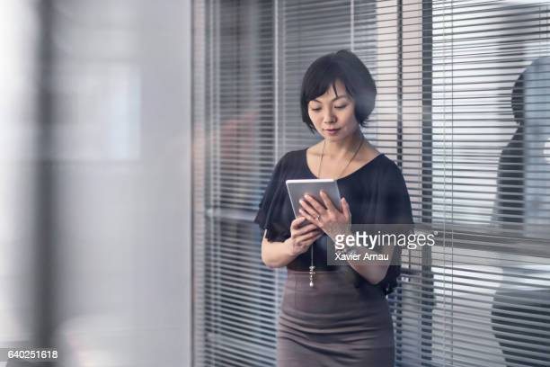 Businesswoman using digital tablet by window