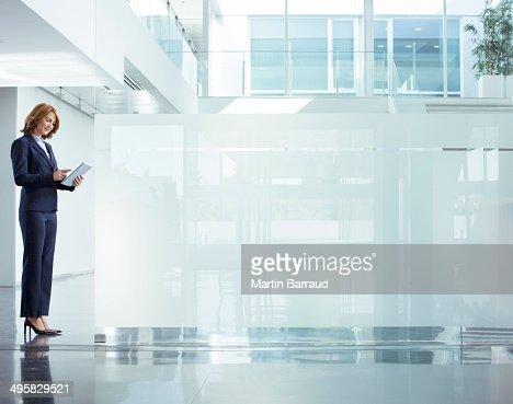 Businesswoman using digital tablet in modern office lobby