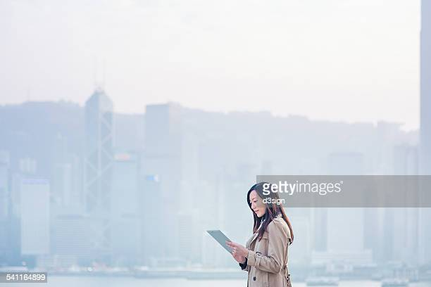 Businesswoman using digital tablet in urban city