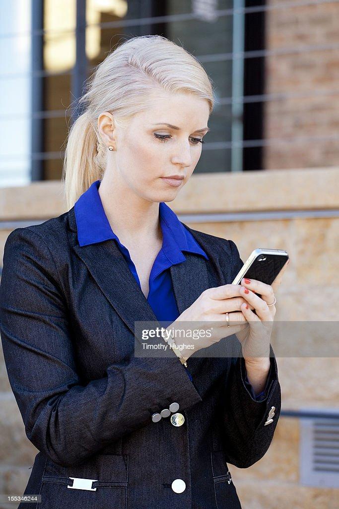 Businesswoman using her smartphone : Stock Photo