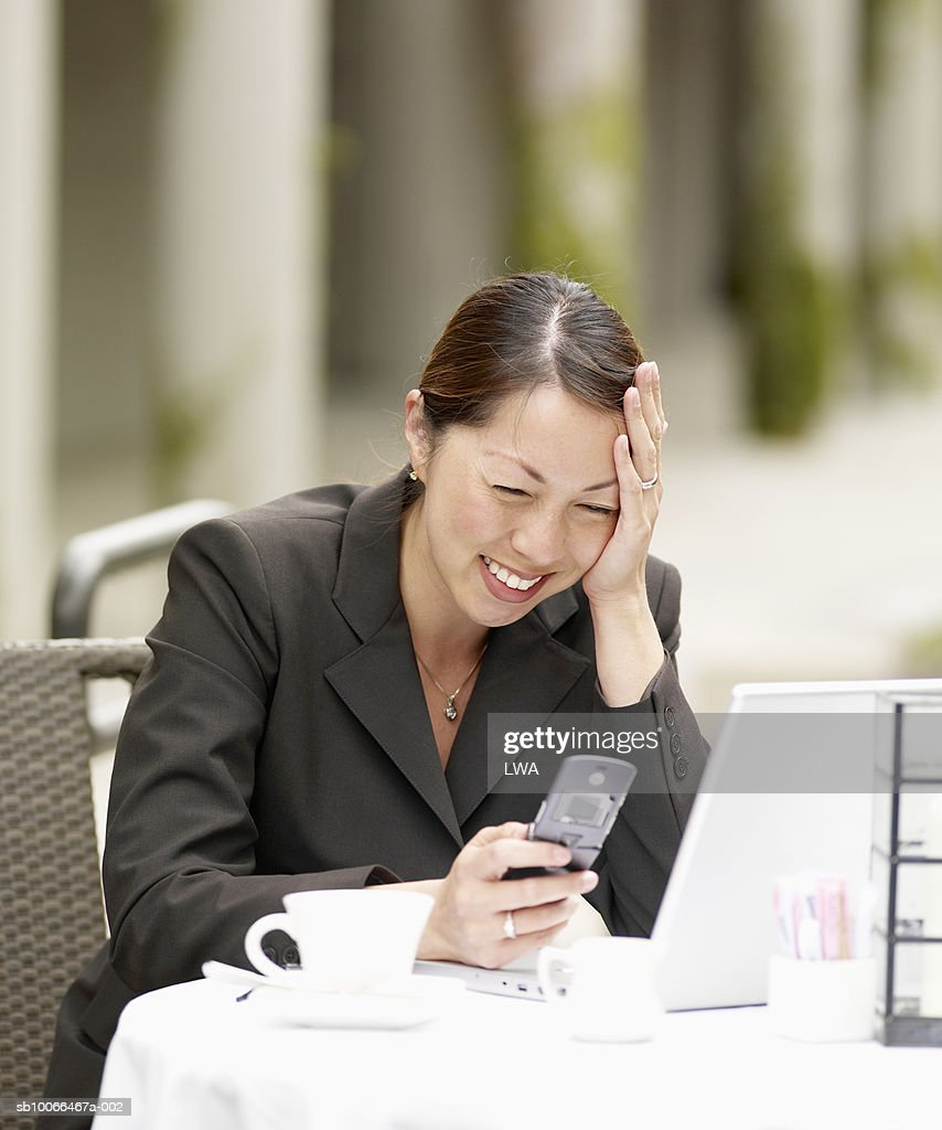 Businesswoman using laptop and mobile phone at pavement cafT, smiling : Stock Photo