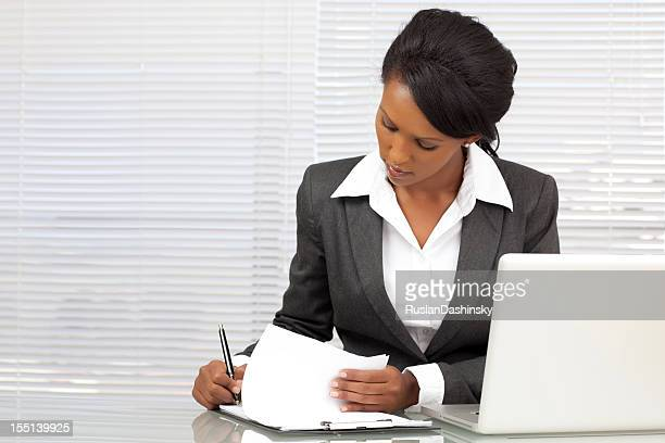 Businesswoman using laptop and preparing reports in office