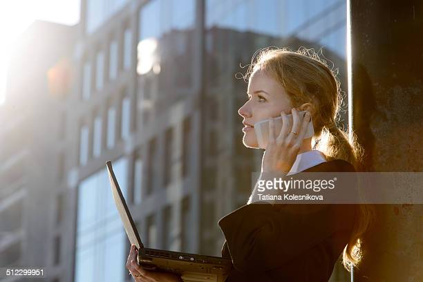Businesswoman using laptop and talking on phone