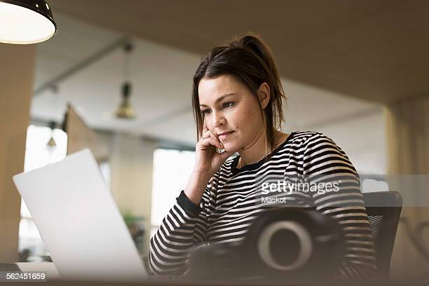 Businesswoman using laptop at desk in creative office