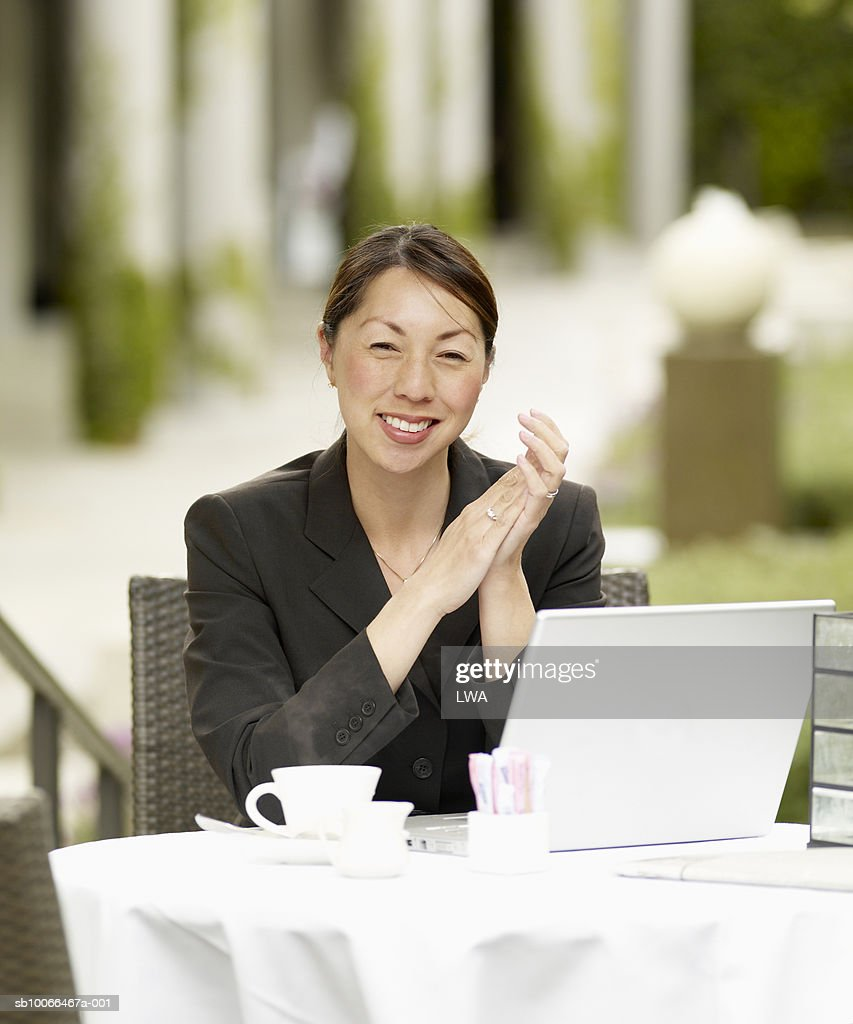 Businesswoman using laptop at pavement cafe, smiling, portrait : Stock Photo