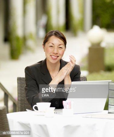 Businesswoman using laptop at pavement cafe, smiling, portrait : Stock Photo