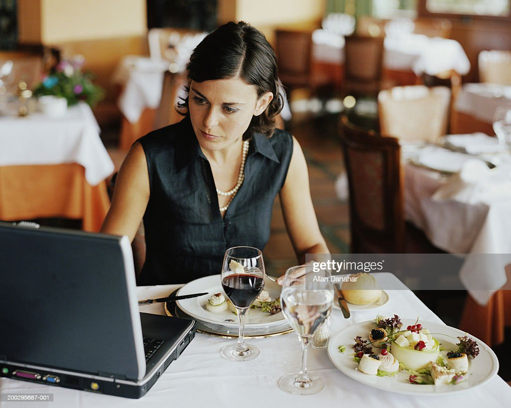 Businesswoman using laptop at restaurant table : Stock Photo