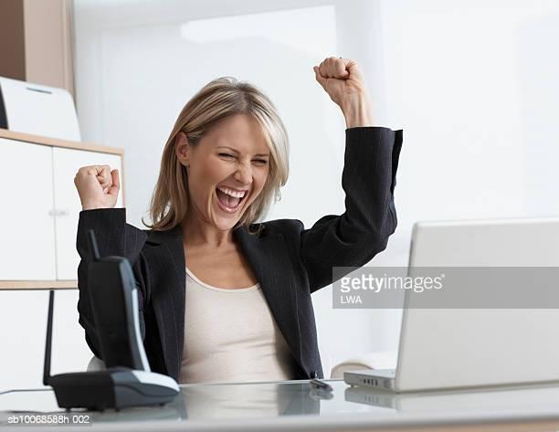 Businesswoman using laptop, cheering