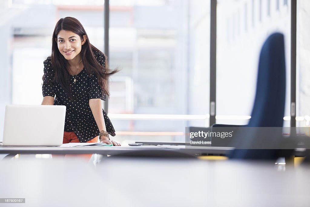 Businesswoman using laptop in modern office : Stock Photo