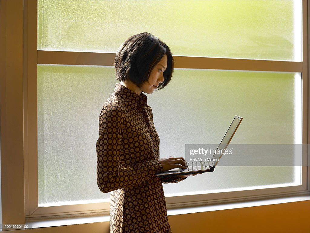 Businesswoman using laptop near window : Stock Photo