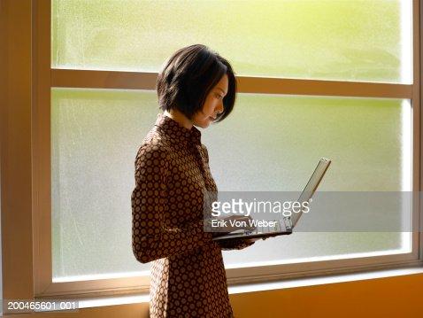Businesswoman using laptop near window : Foto de stock