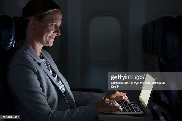 Businesswoman using laptop on airplane