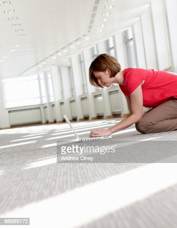 Businesswoman using laptop on floor in empty office : Stock Photo