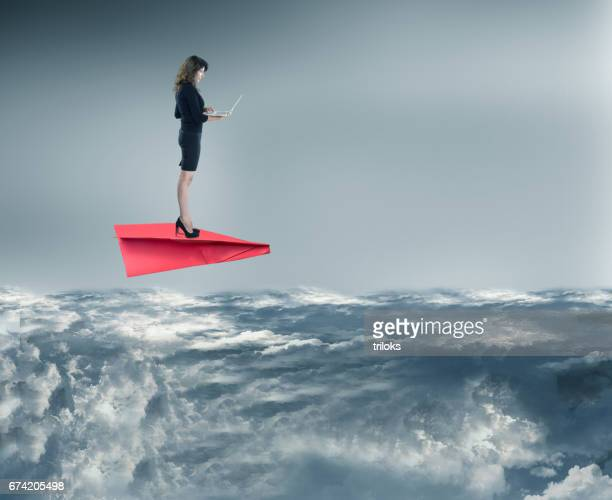 Businesswoman using laptop on paper airplane while flying over clouds