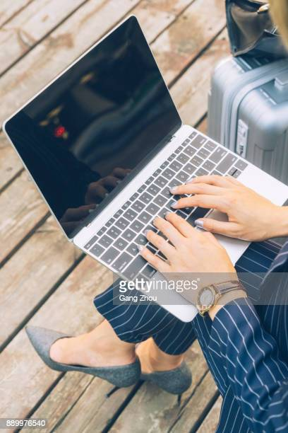 businesswoman using laptop on park bench with suitcase on side