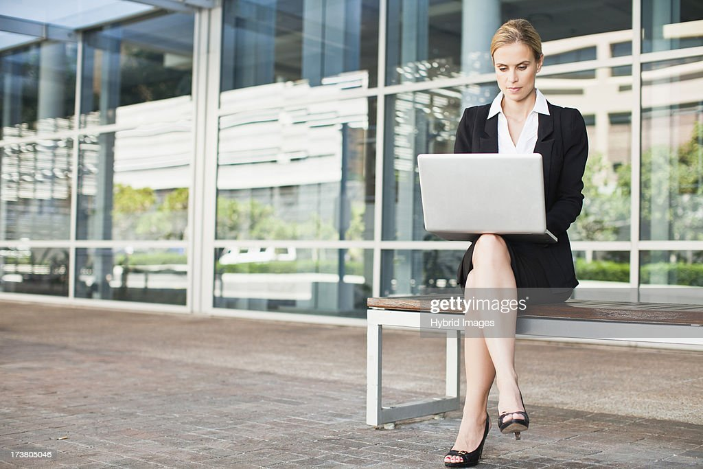 Businesswoman using laptop outdoors : Stock Photo