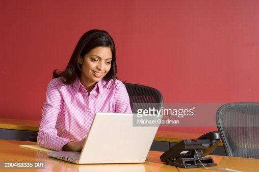 Businesswoman using laptop, smiling : Stock Photo