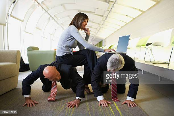 Businesswoman Using Laptop While Sitting on Businessmen