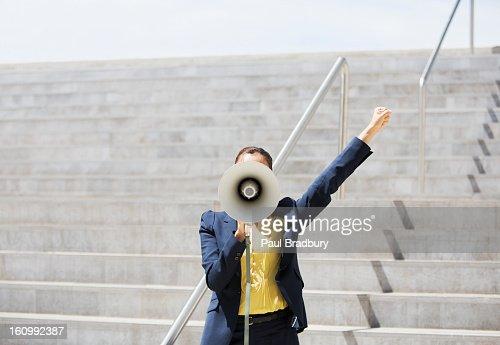 Businesswoman using megaphone on urban steps